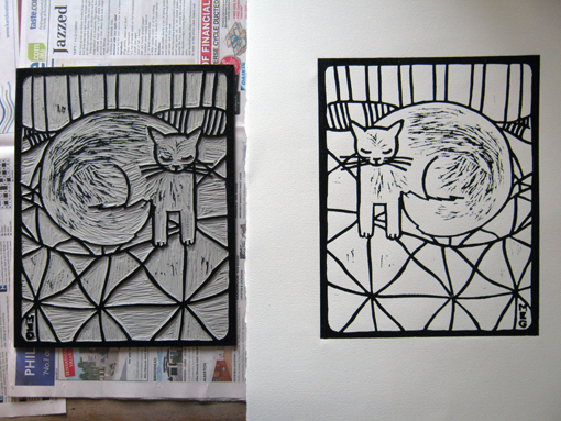 inked lino block of a cat picture next to a fresh print on white paper