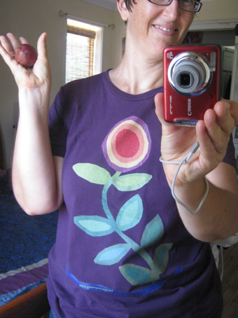 "self portrait by and including my red camera, whilst also holding a plum and wearing a flower tshirt after my picture ""Thriving"""