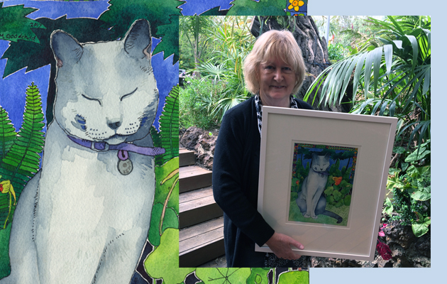 A custom cat portrait of Lewis and a photo of his family member holding the framed picture
