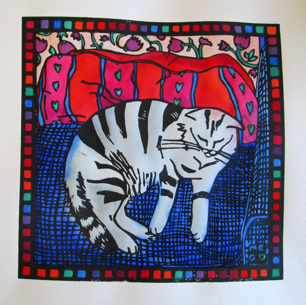 Lino print of black and grey cat on blue sofa with pink and red patterned cushion