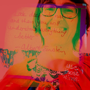 Intensely coloured double exposure self portrait in a red cape with overlaid Albert Einstein quote in my writing