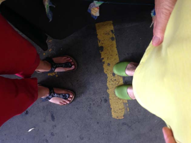 2 people looking down at their feet in a carpark; the person on the left has red pants and black sandals with flowers, the person on the right has yellow clothing and green shoes. On the ground is a worn yellow painted car park divider line.