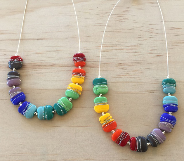 2 rainbow glass necklaces on wooden background