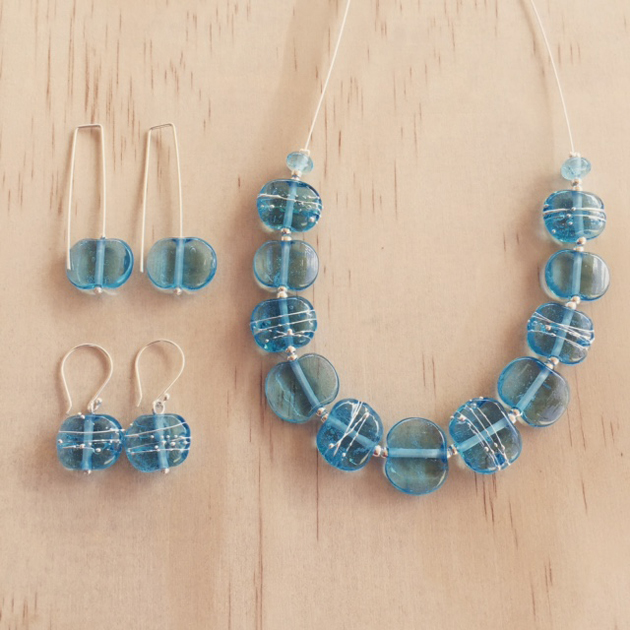 light blue glass necklace and earrings displayed on wood background