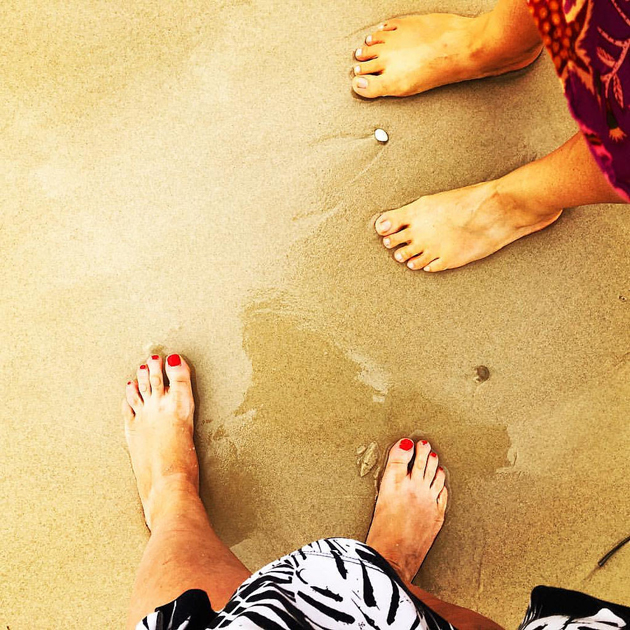 bare feet of 2 humans in skirts, the one taking the photo has applied nail polish, the feet are at a sandy beach