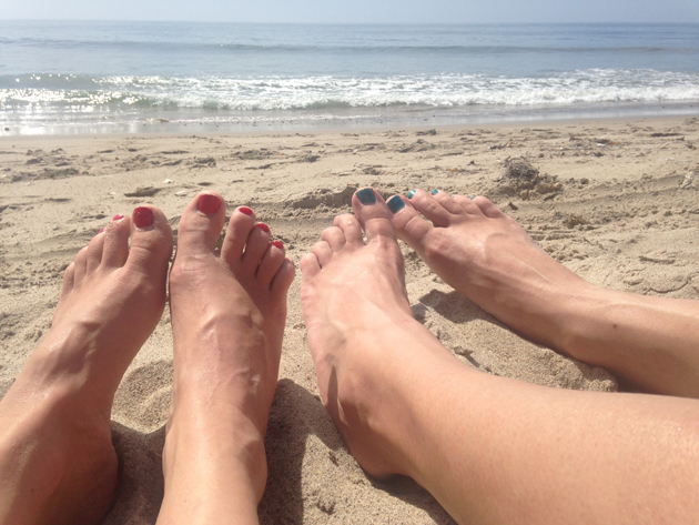 2 pairs of human feet, both with nail polish, at a sandy beach with the ocean in the background