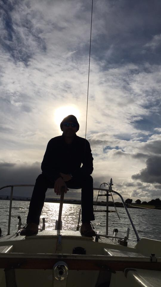 silhouetted fisherman on boat with cloudy sky behind