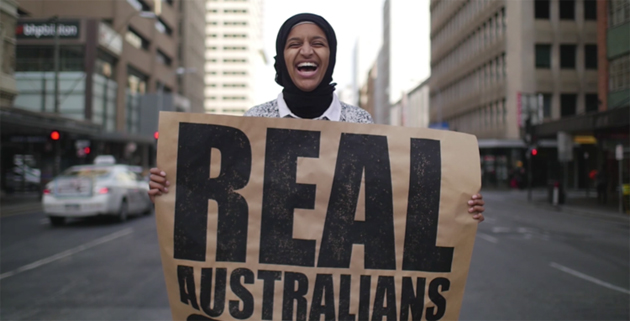 Happy women holding 'Real Australians Say Welcome' in a city street