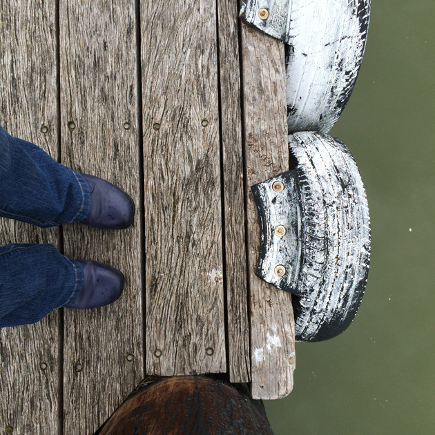 looking downwards at blue jeans and shoes standing on wooden wharf with white painted tyres attached to the edge and green water below