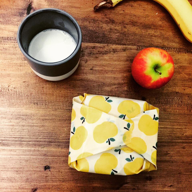 A cup of milk, an apple, a banana and a snack wrapped in a yellow apple patterned food wrap, on a wooden surface.
