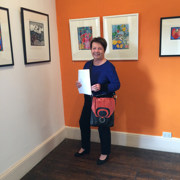 Smiling woman in blue top and holding red and black graphic design bag, standing near art exhibition works hung on 2 walls, one wall of which is painted orange.