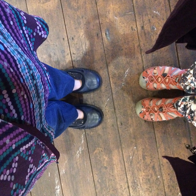 Camera looking down and 2 people facing each other's shoes standing on dark wood floor