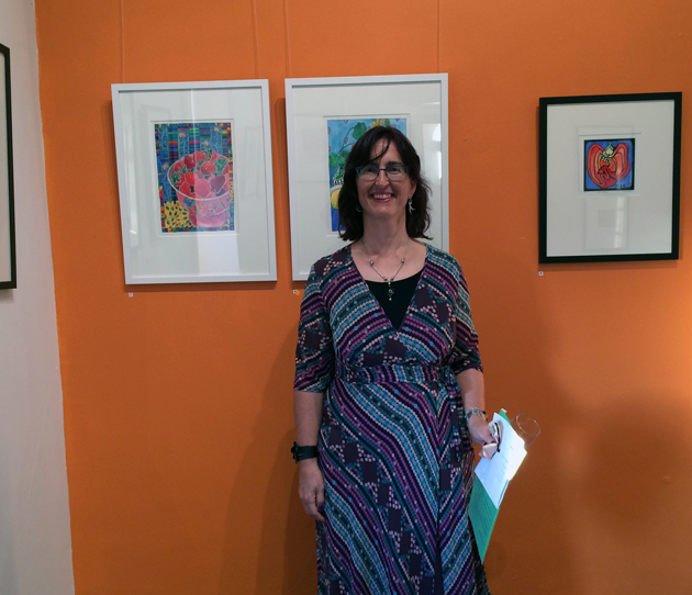 South Australian woman artist, Tangerine Meg, wears a purple and green/blue spotty dress, and stands in front of an orange wall with framed pictures hanging on it.