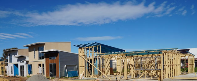 a row of houses under construction under a very blue sky