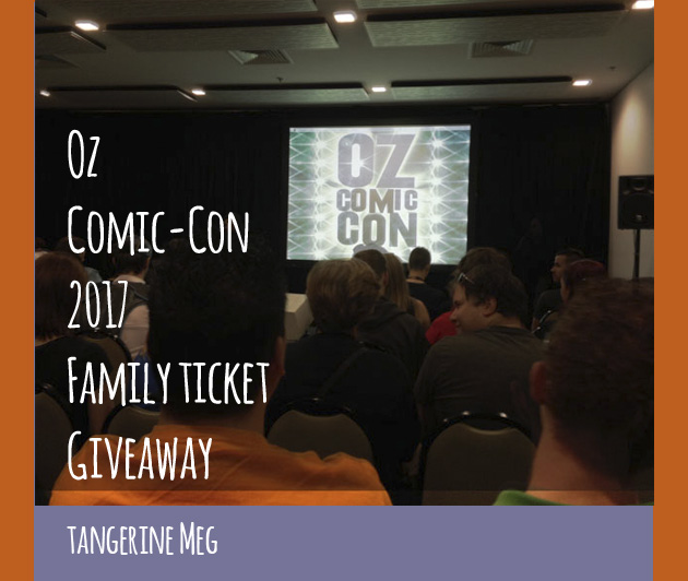 "photo of convention room, showing audience heads chatting while they wait for a talk; on stage is a screen with the 2014 Oz Comic-Con logo of 2014; overlaid is blog post header in hand-writing looking font stating: "" Oz Comic-Con 2017 Family Ticket Giveaway - Tangerine Meg"". There's a purple border at the bottom and orange borders at the sides."
