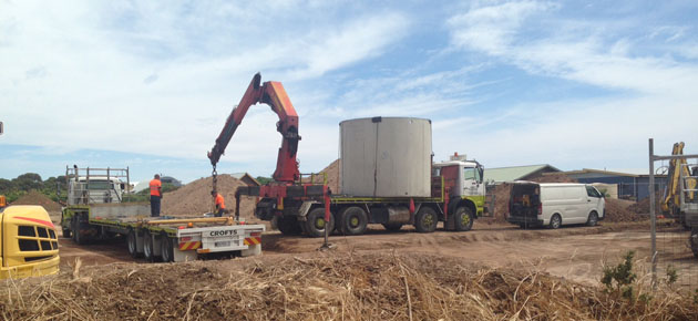 Trucks and machinery delivering a big concrete water tank