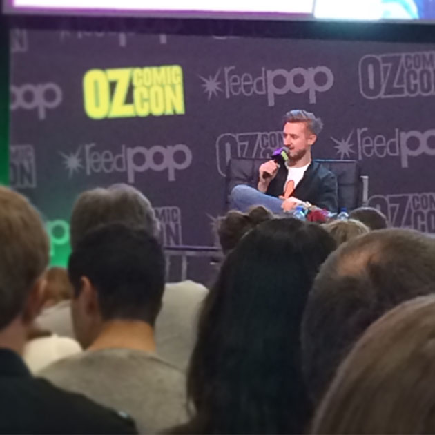 "Audience members facing away from the camera, towards a man with a microphone talking on stage. The man's backdrop is patterned with ""Oz Comic Con"" and ""reed pop"" logos."
