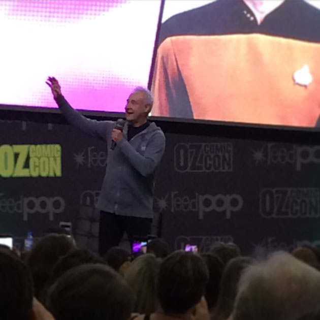 An Oz Comic-con audience is watching a man gesturing on stage. The background is a cropped Star Trek uniform.