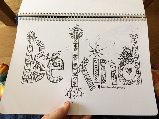 "left hand holding a page of a spiral bound book with ""Be Kind"" typographic illustration marker drawing"