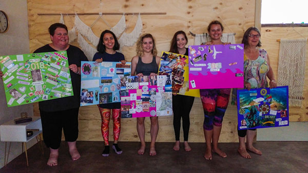 6 beautiful souls holding up their vision boards for 2018 in a wood-lined yoga studio