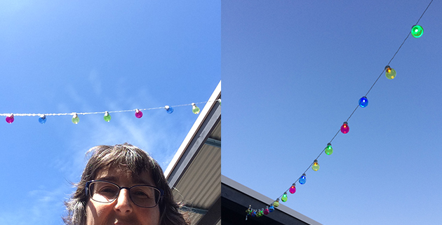 party lights installed and lit and a half face selfy, all with blue sky, right hand side deeper blue