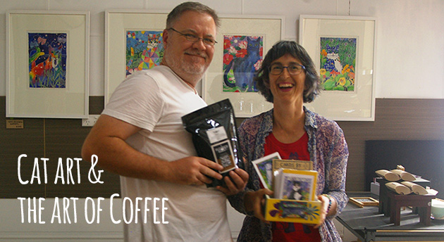 Laughing lady holding box of cards, and smiling man holding shiny black bag of custom roasted coffee, with a group of cat paintings in the background.