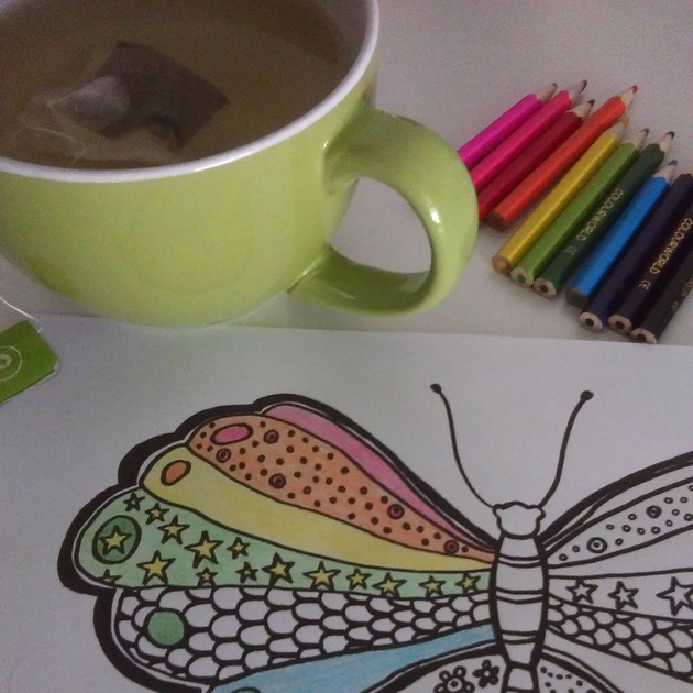 cup of tea and coloured pencils alongside line drawing of butterfly being coloured in rainbow-like