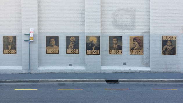 full set of 7 AUSSIE posters by Peter Drew Arts, pasted on a white wall with the road showing in the foreground, with yellow dashed painted markings