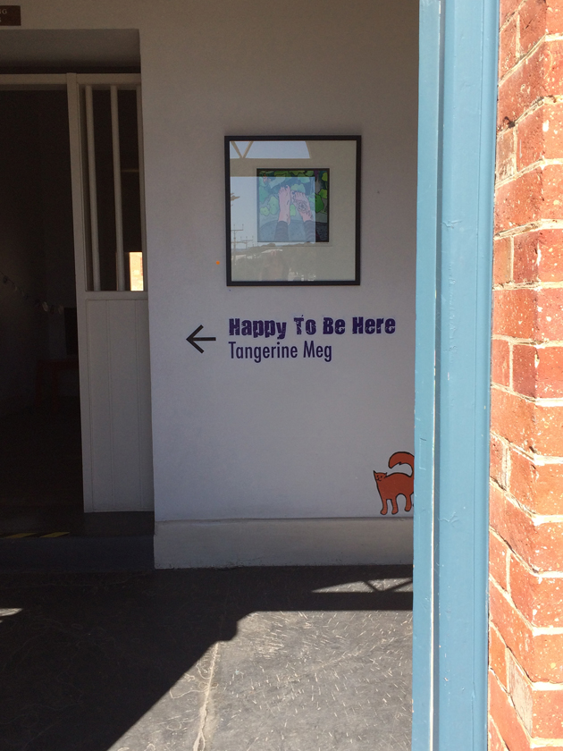 """Looking into a red brick building through a blue door frame, is seen a white wall with a painting displayed. Underneath the picture are the words """"Happy To Be Here"""" and """"Tangerine Meg"""" with an arrow pointing left, and a sticker of an orange cat perched just above the skirting board."""