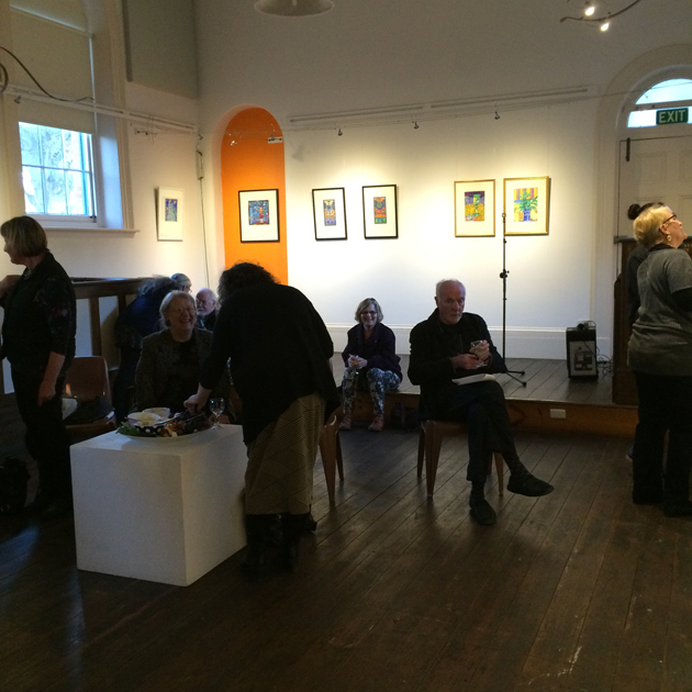 delightful bold souls mingling, chatting and smiling at the launch of Happy to Be Here exhibition; the room is high of ceiling, with walls lined with framed pictures; the floor is dark timber.