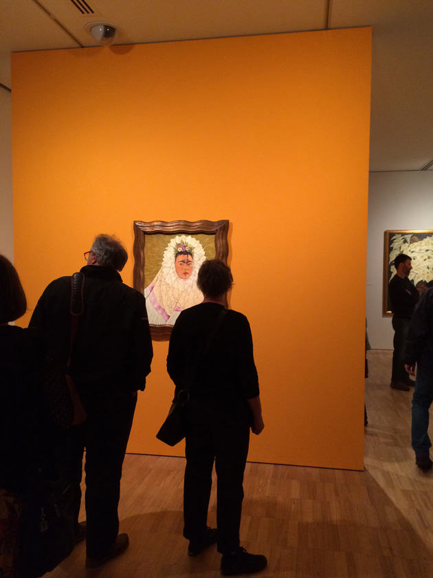 Backs of people viewing Frida Kahlo painting on orange wall.