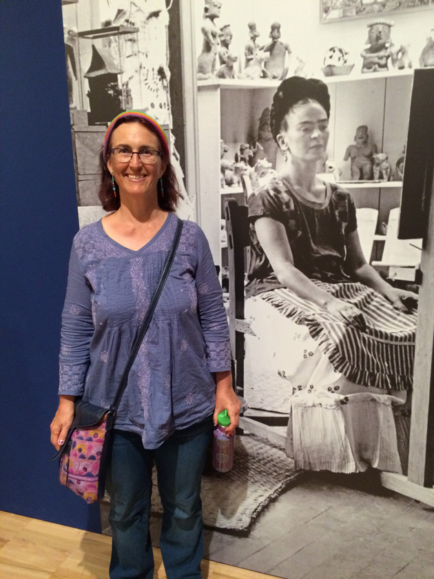 Tangerine Meg posing smiling in blue shirt in front of black and white photo mural of Frida Kahlo in her studio.