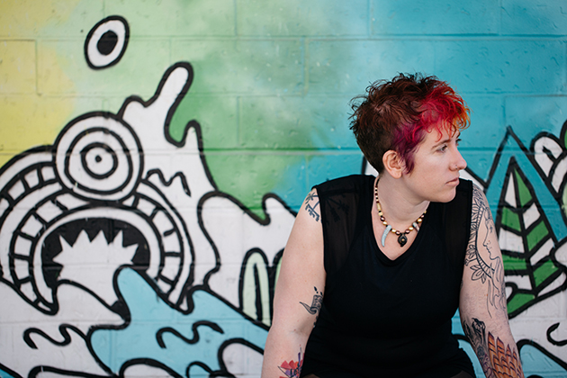 Michelle Nickolaisen seated in front of a graffiti wall with black drawings and lots of green and blue. She's looking out of the photo to our right.